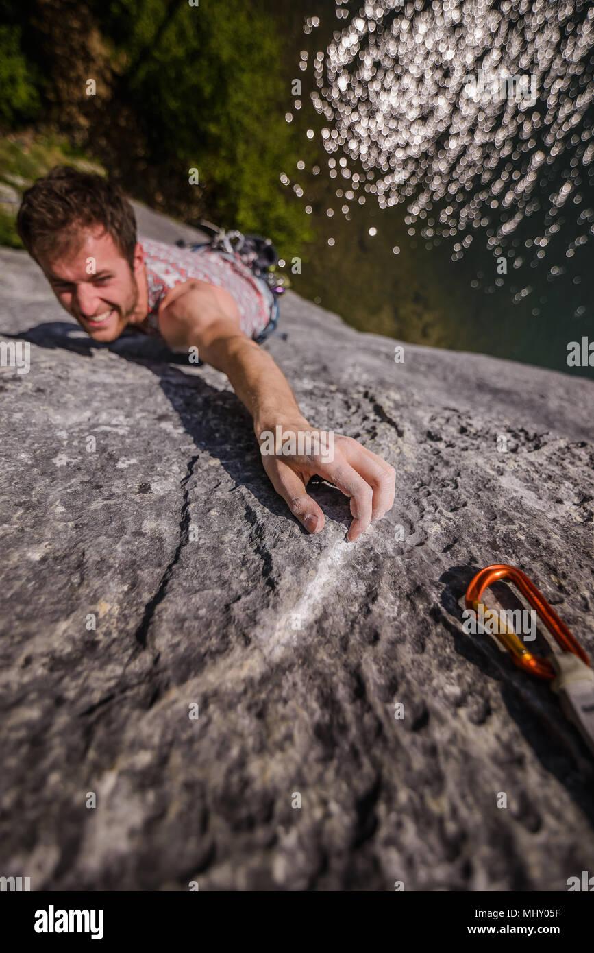 Giovane maschio rocciatore raggiungendo mentre arrampicata su roccia calcarea faccia, Freyr, Belgio, ad alto angolo di visione Immagini Stock