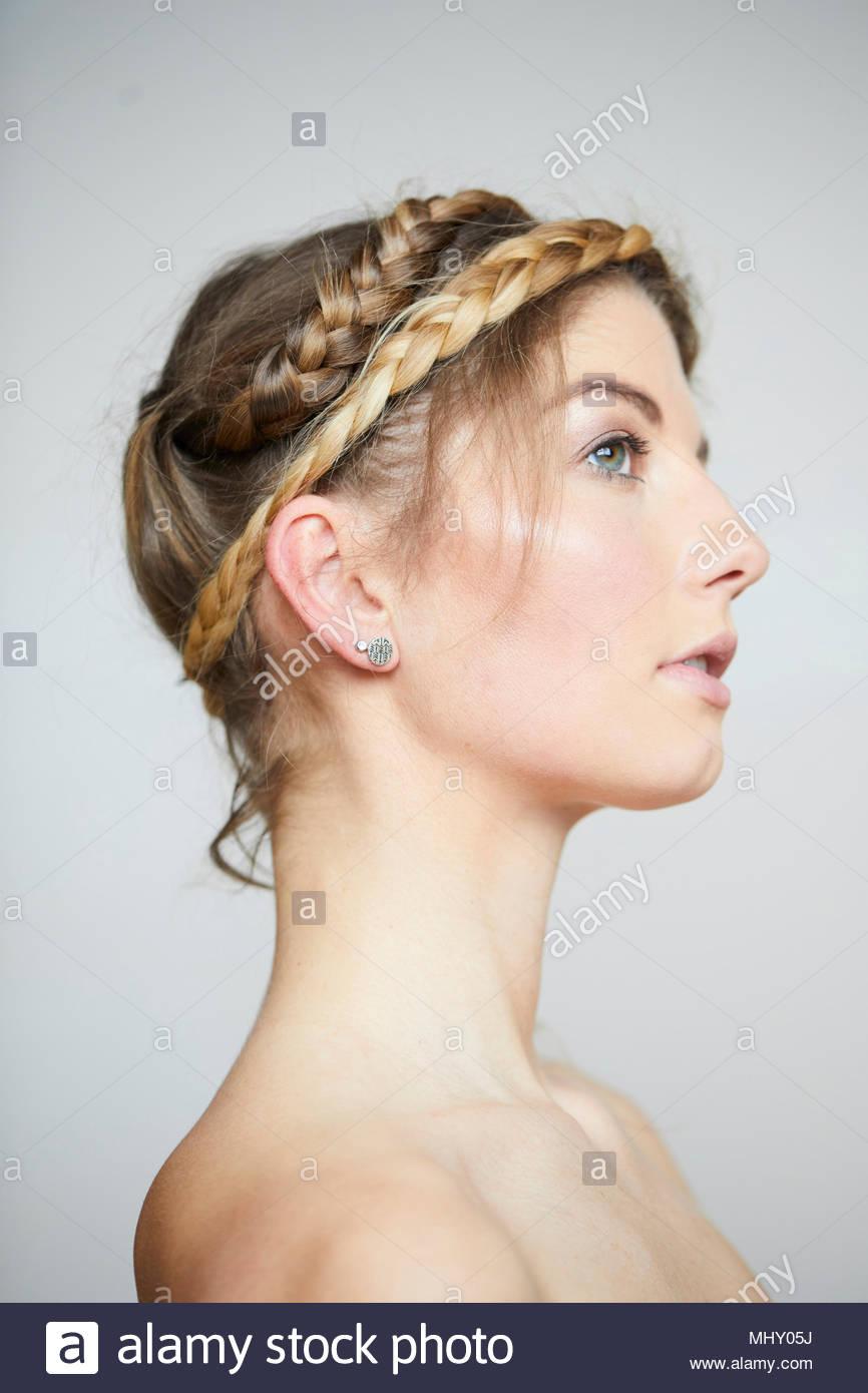 Bella giovane donna con le spalle nude e capelli intrecciati, vista laterale ritratto in studio Immagini Stock