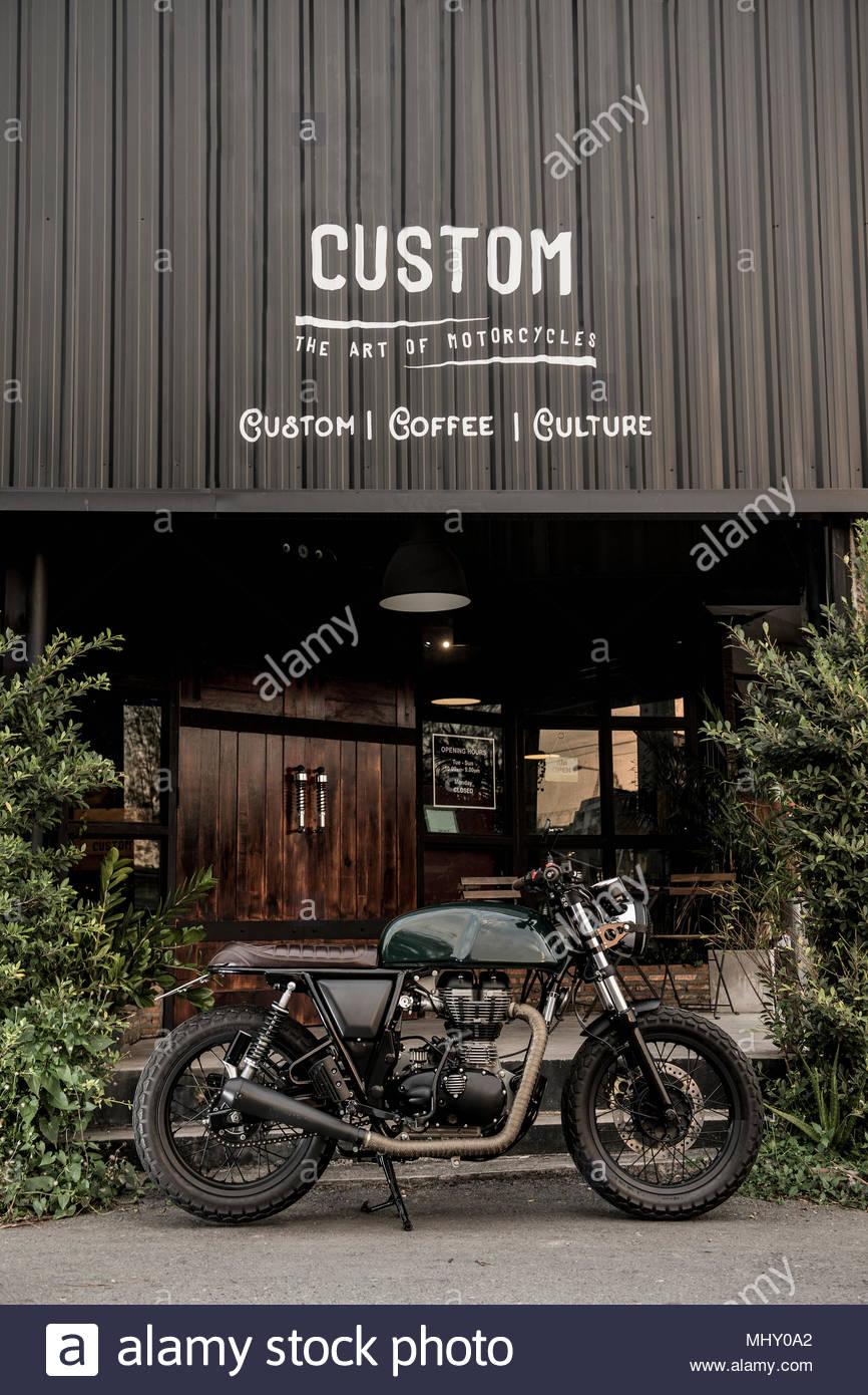 Cafe racer moto parcheggiata fuori moto personalizzate e coffee shop, Bangkok, Thailandia Immagini Stock