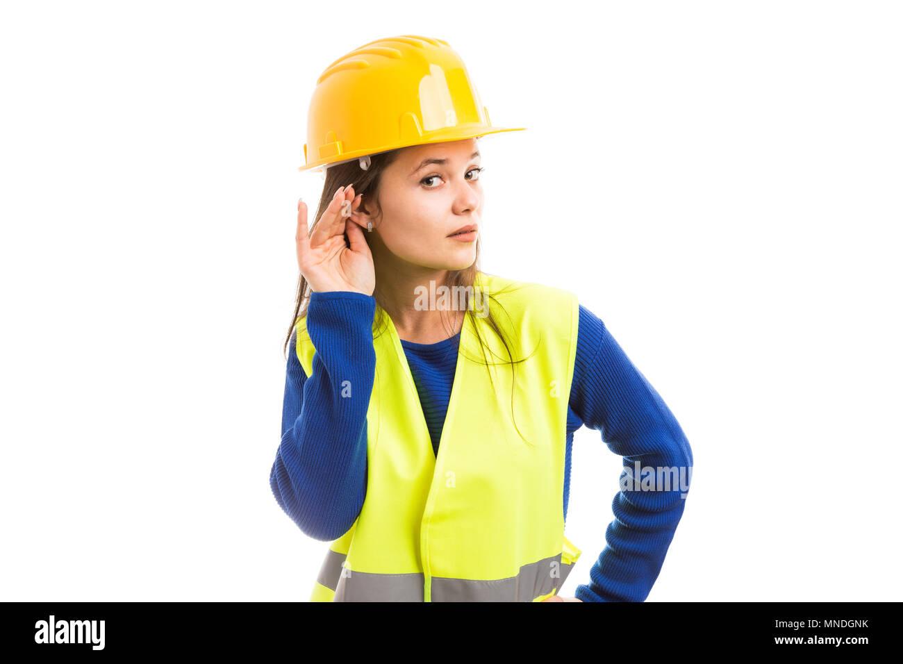 Giovani attraenti ingegnere femmina facendo sentire gesto toccando il suo orecchio come prestando attenzione al concetto di pettegolezzo isolati su sfondo bianco Immagini Stock