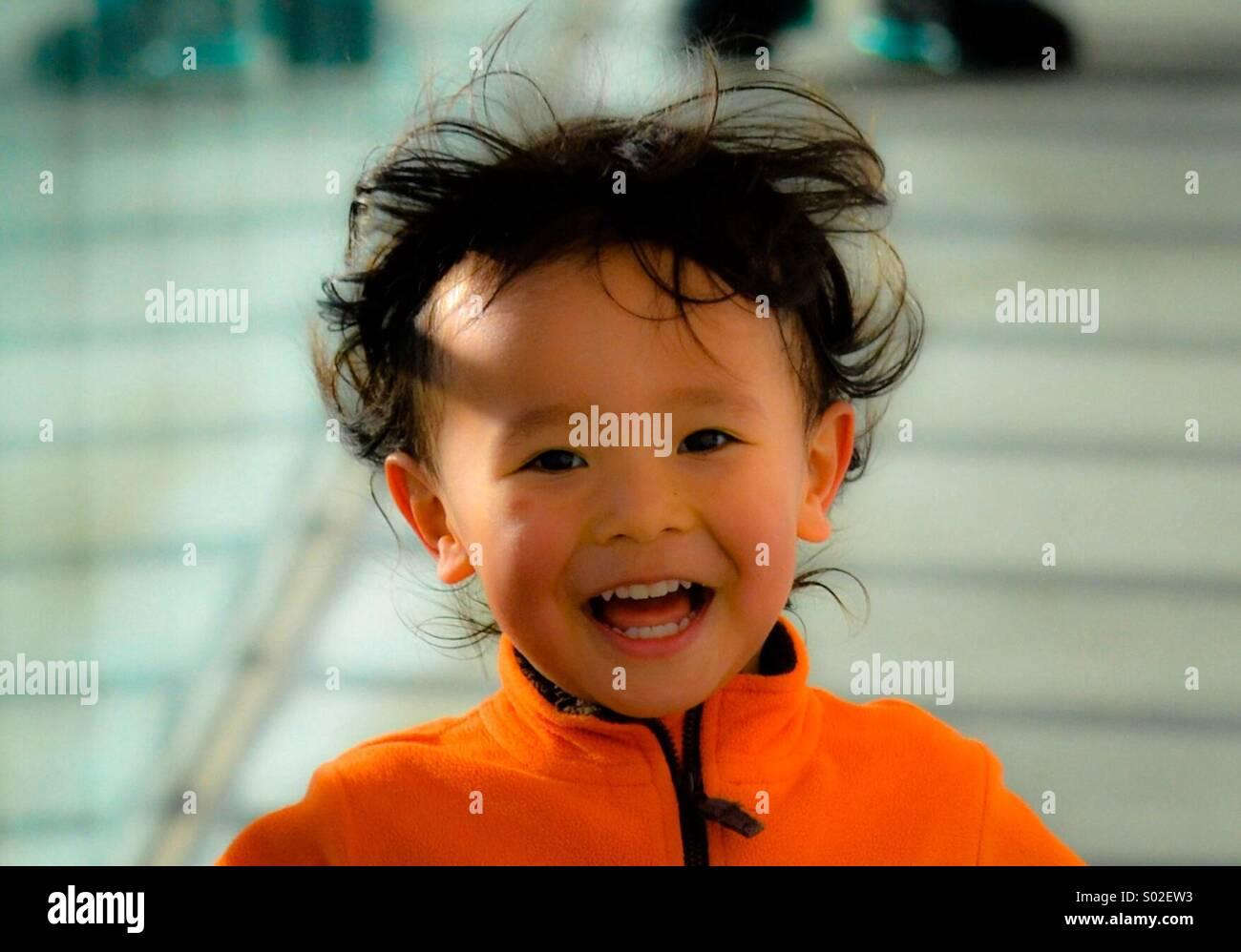 3 anno vecchio Luis S. del Giappone corre e lough wile guardando la telecamera a Rinkaekoen Park a Tokyo. Foto di: Immagini Stock