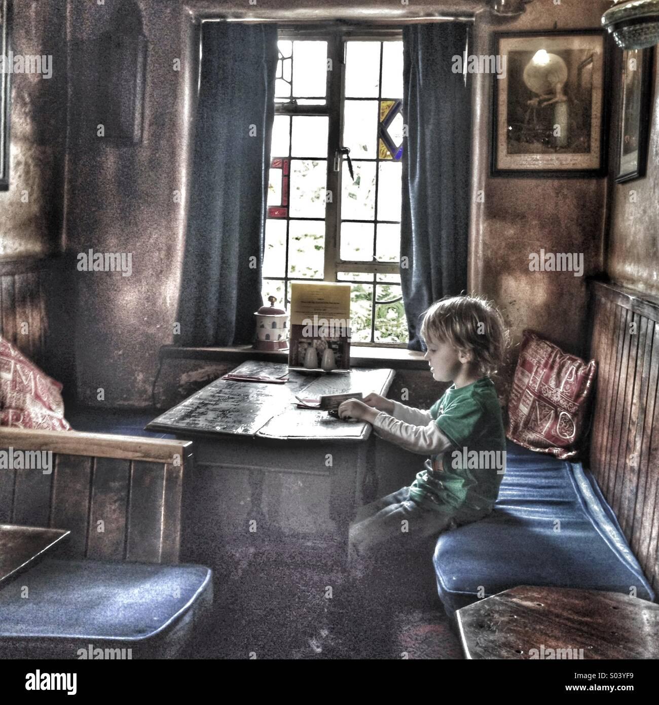 Ragazzo seduto sul suo proprio in corrispondenza di una tabella in un vecchio pub Immagini Stock