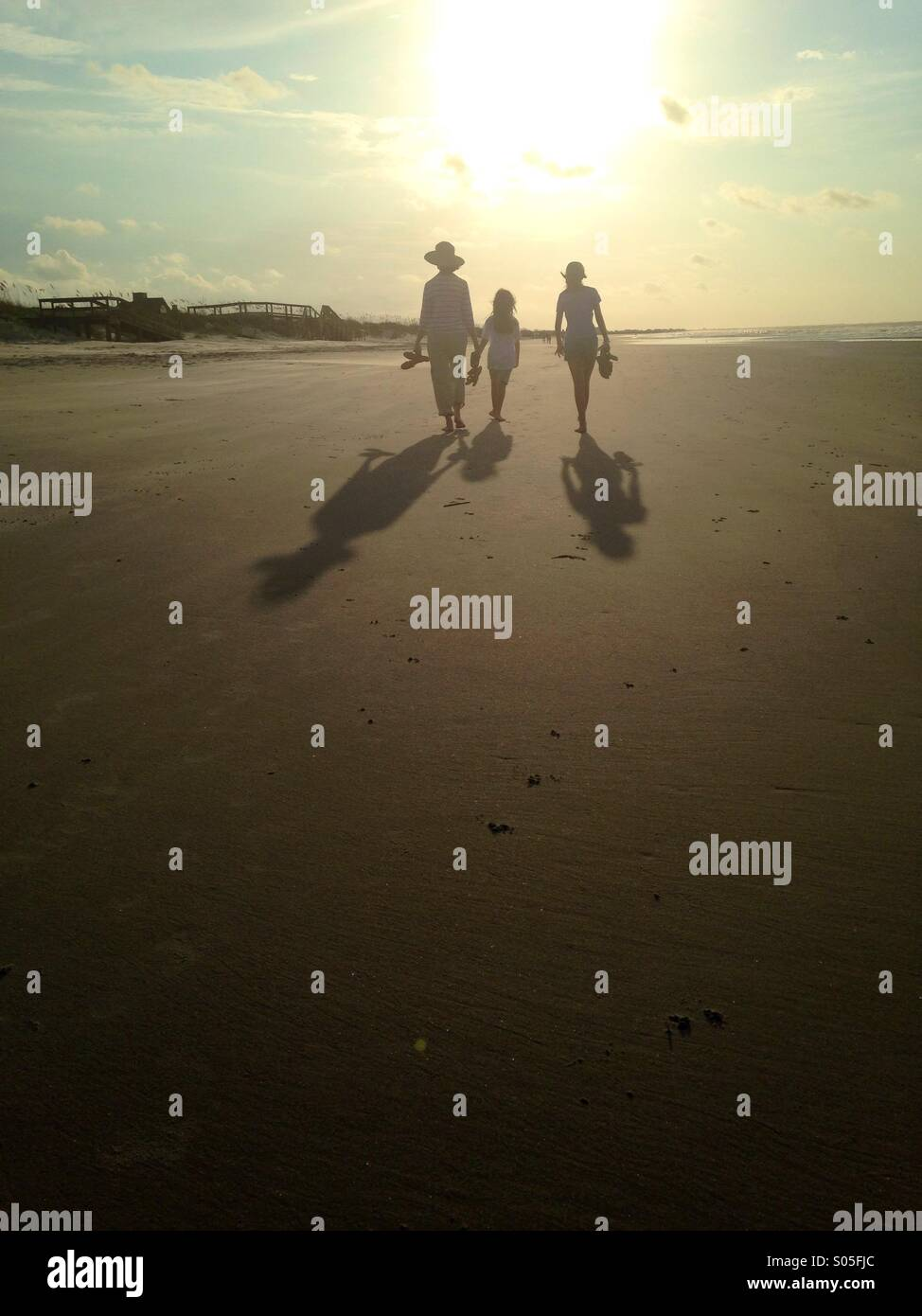 Le sagome di tre persone a piedi lungo la spiaggia nella luce del mattino. Immagini Stock