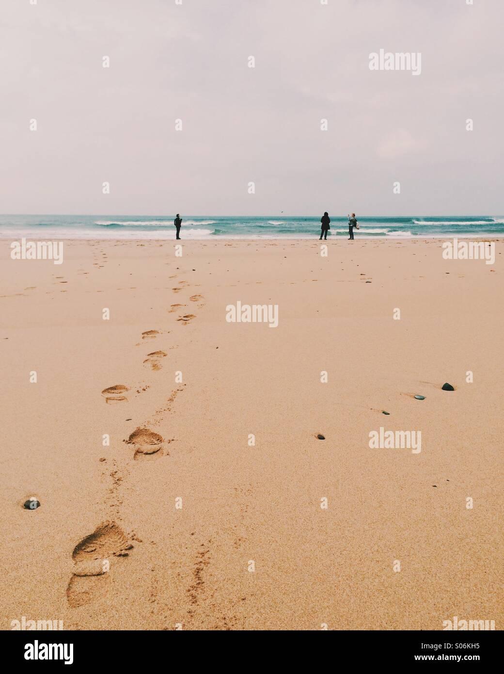 Tre persone su una spiaggia Immagini Stock