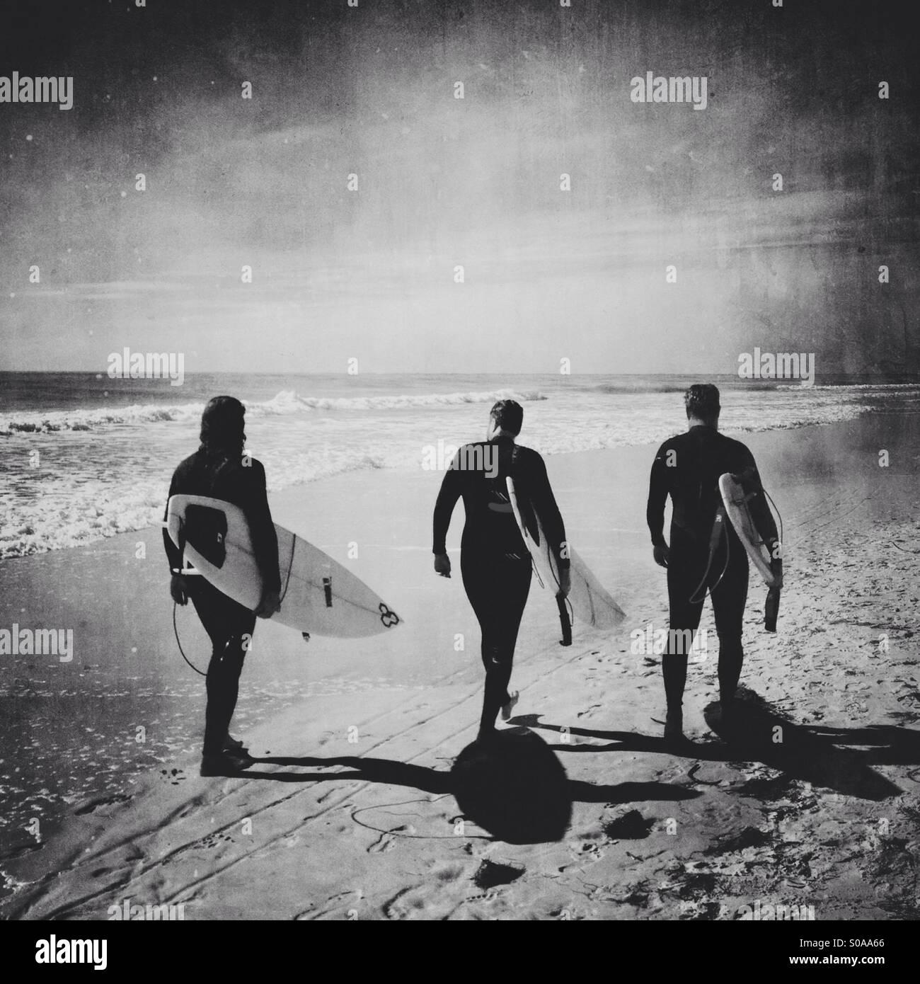 Tre surfers passeggiando lungo la spiaggia. Immagini Stock