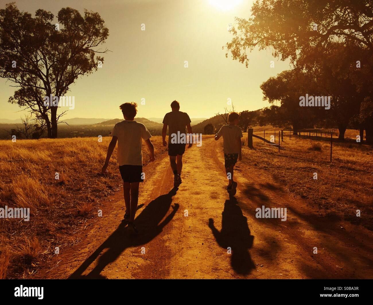 Un padre e i suoi due figli la riattivazione nel tramonto nel Paese Australia Immagini Stock