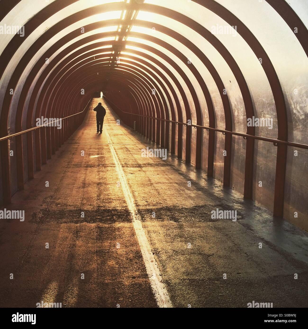 Una silhouette di un uomo che cammina verso il basso un tunnel a sunrise in Glasgow Immagini Stock