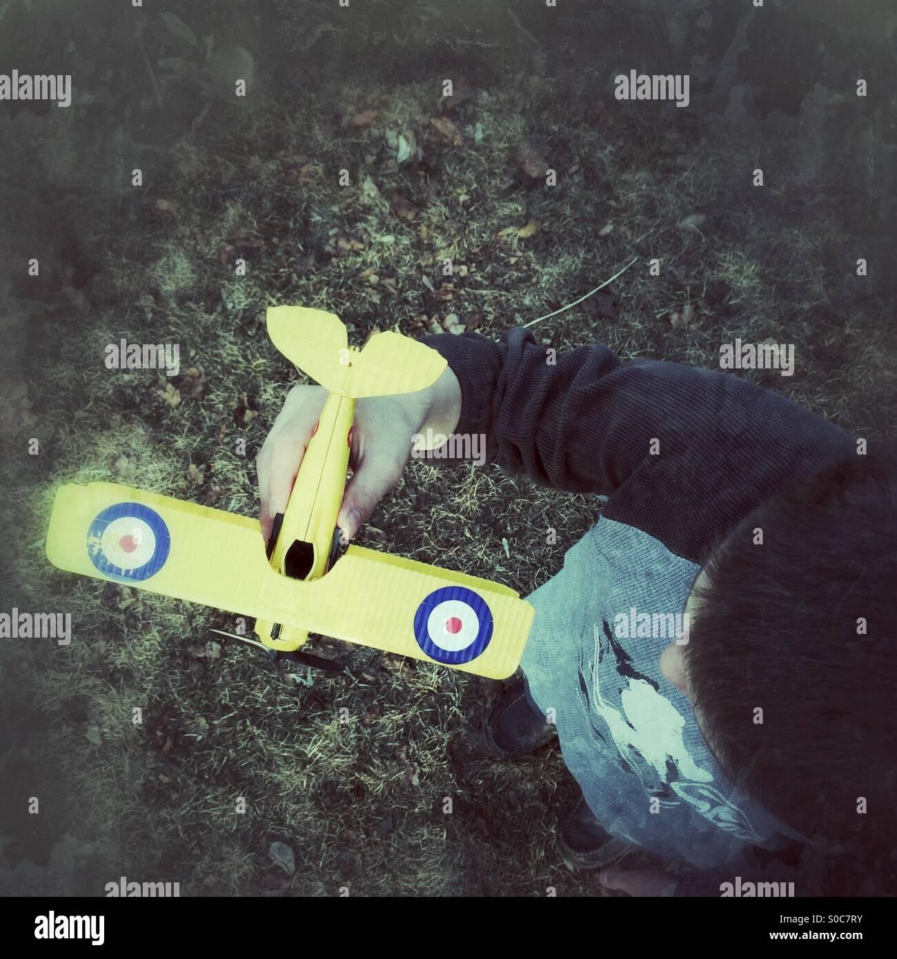 Guardando verso il basso in corrispondenza di un ragazzo tenendo un modello di aeroplano Immagini Stock