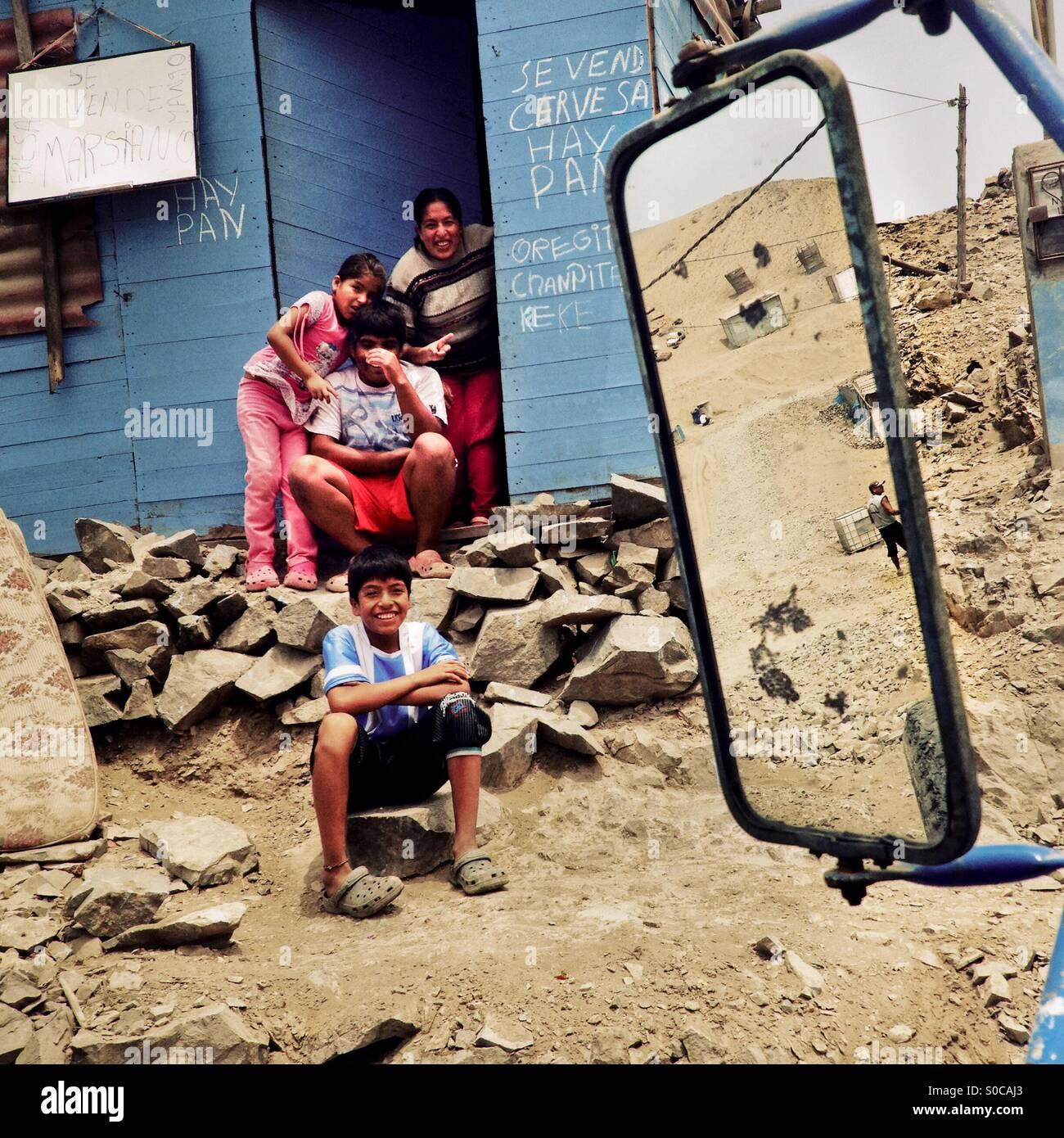 Famiglia Peruviana membri siedono davanti a una casa in legno sulla polvere della collina di Pachacútec, un Immagini Stock