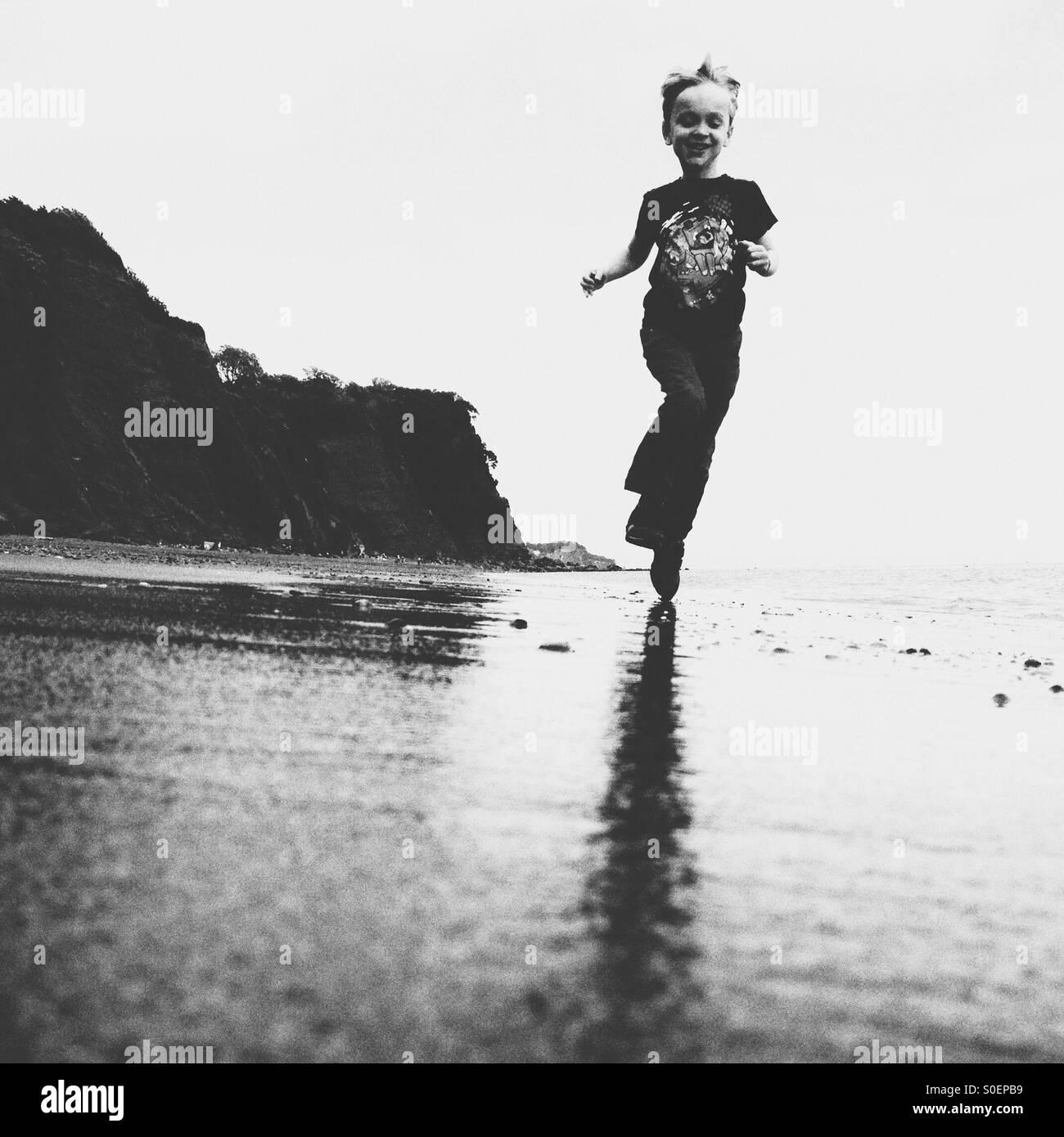 Ragazzo in esecuzione su una spiaggia Immagini Stock