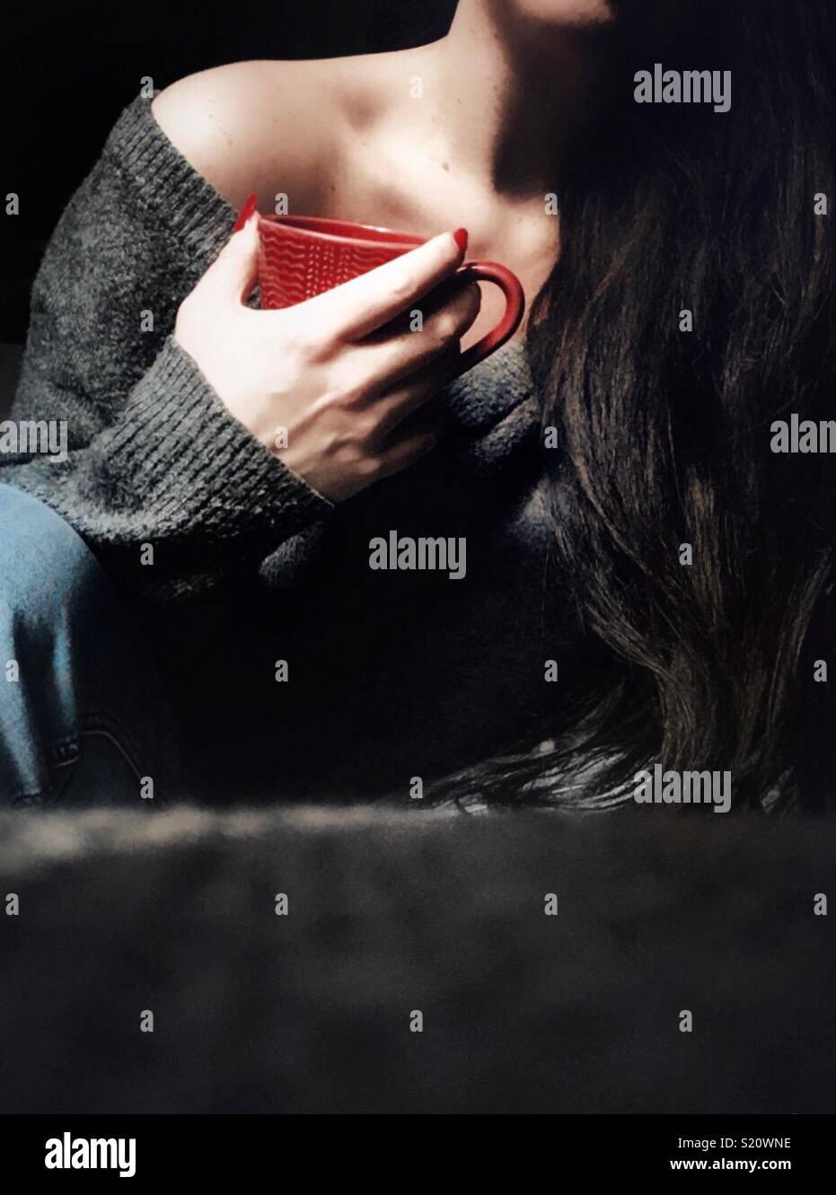 Donna con lunghi capelli scuri tenendo un bicchiere di rosso Immagini Stock