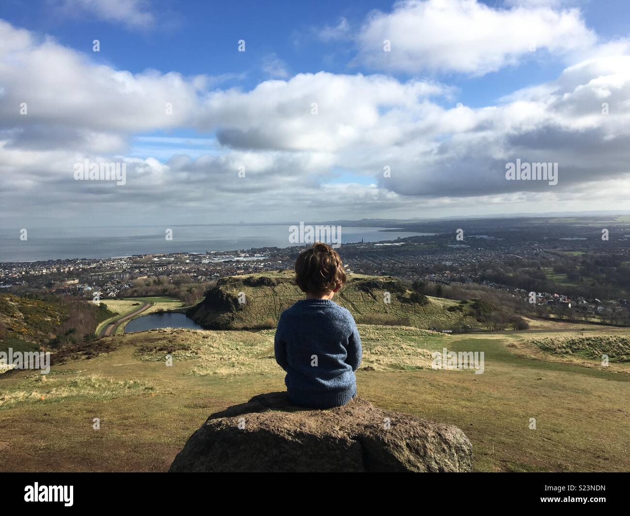 Ragazzo seduto alla Arthur' Seat, Edimburgo Immagini Stock