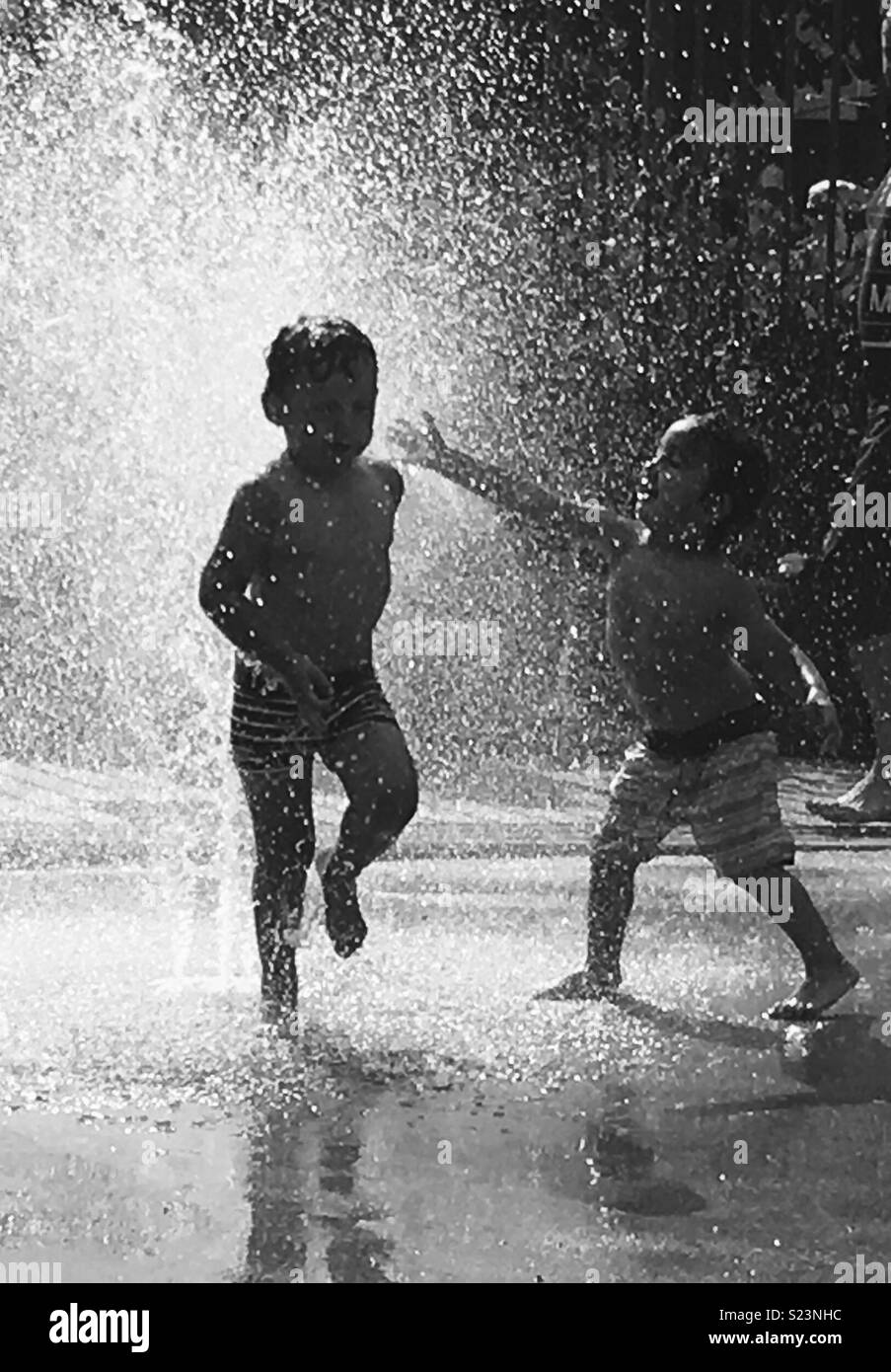 Bambini divertirsi nella fontana durante le calde giornate estive Immagini Stock