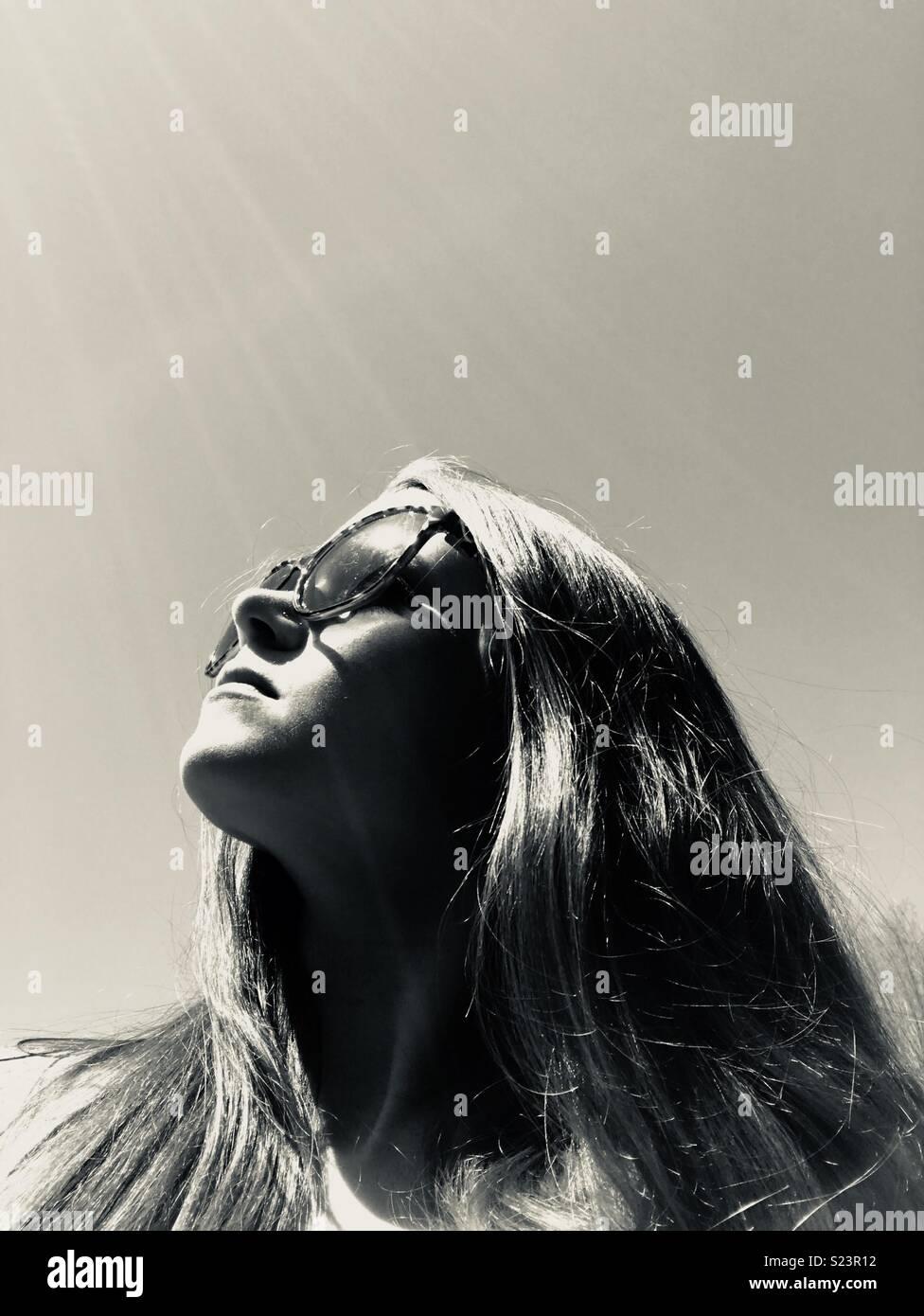 Sole che splende in giù sulla ragazza con occhiali da sole Immagini Stock
