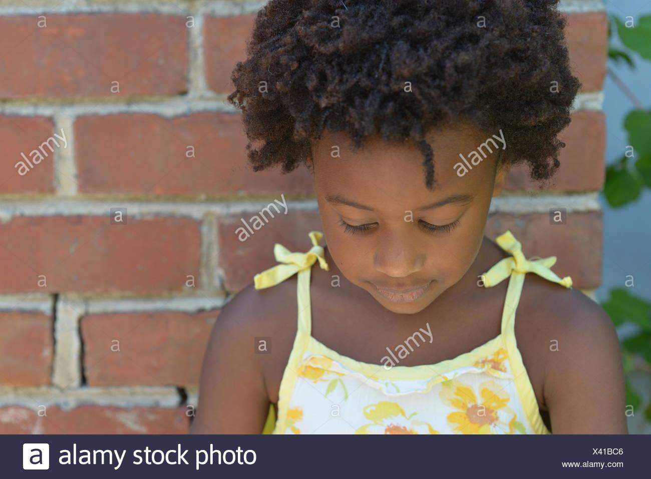 Le ragazze in piedi da un muro di mattoni guardando verso il basso Immagini Stock
