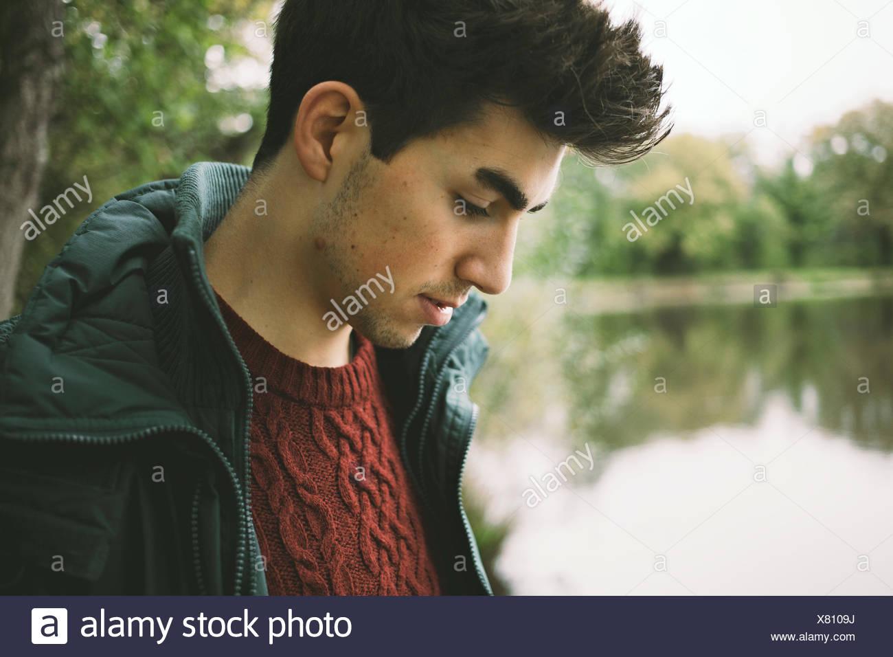 Ravvicinata di un giovane uomo che guarda il riverbank Immagini Stock