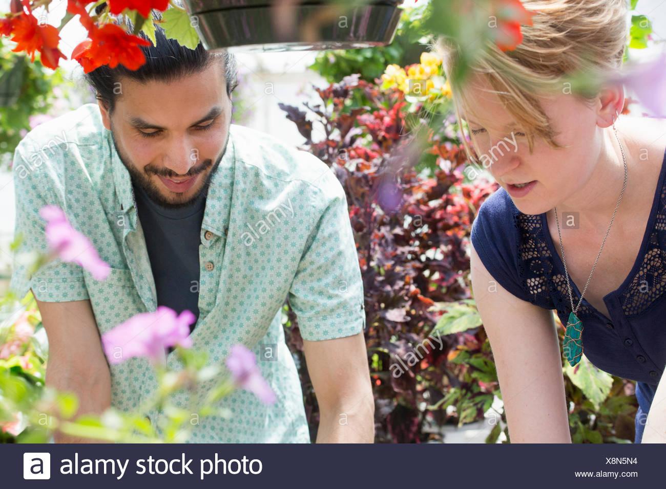 Un uomo e una donna in un centro giardino, sia guardando verso il basso. Immagini Stock