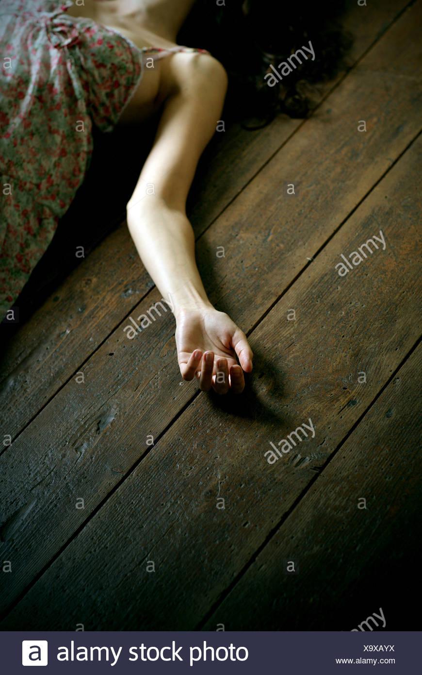 Dead donna sdraiata sul pavimento, focus sulla mano Immagini Stock