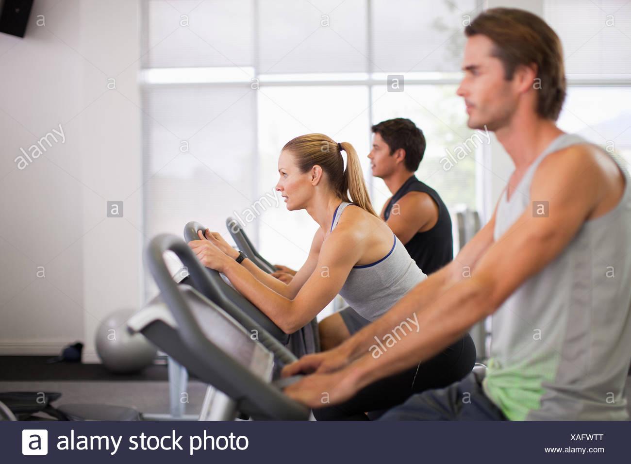 Tre persone sulla cyclette in palestra Immagini Stock