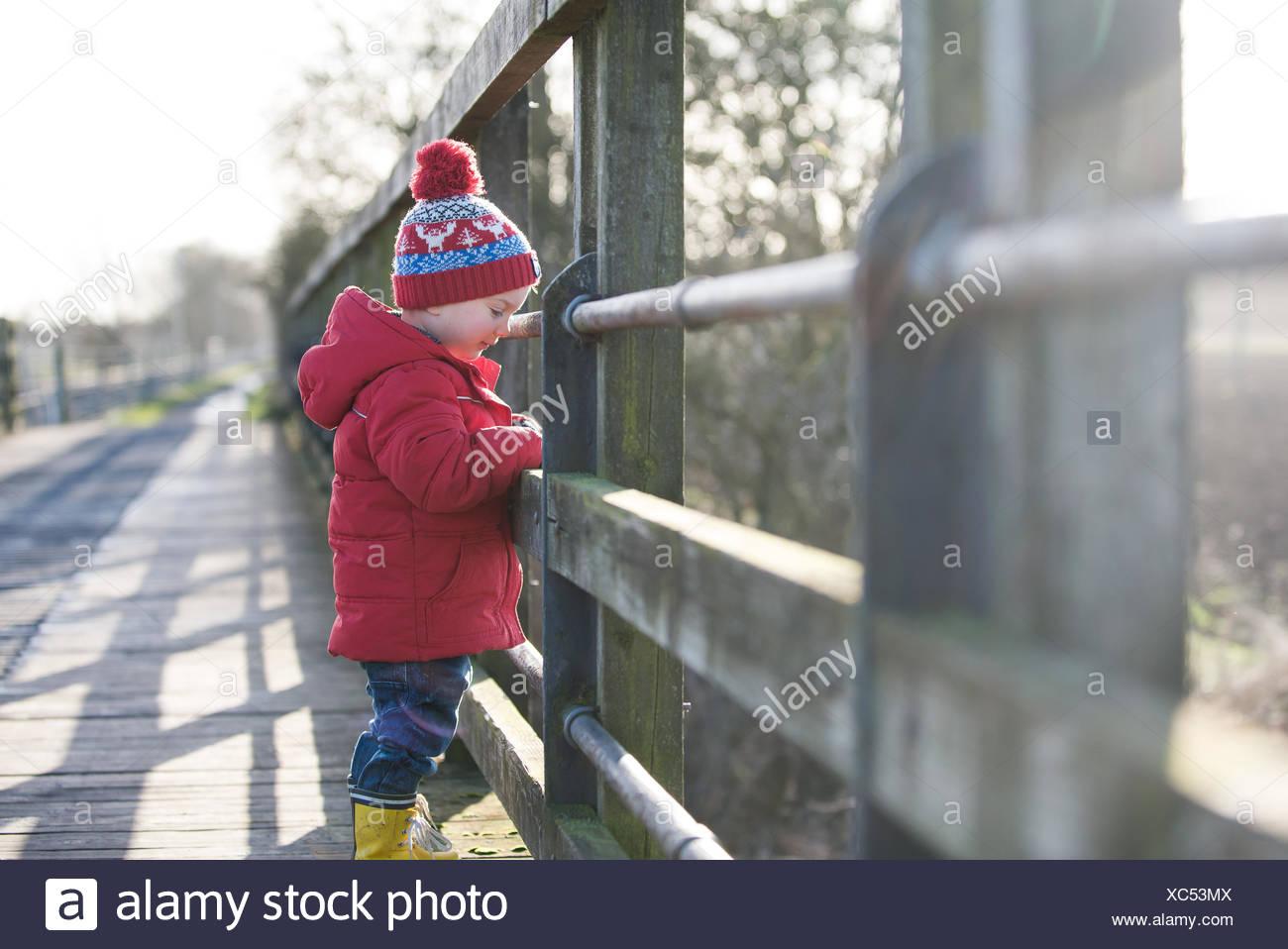 Ragazzo in piedi su un ponte guardando giù al fiume Immagini Stock