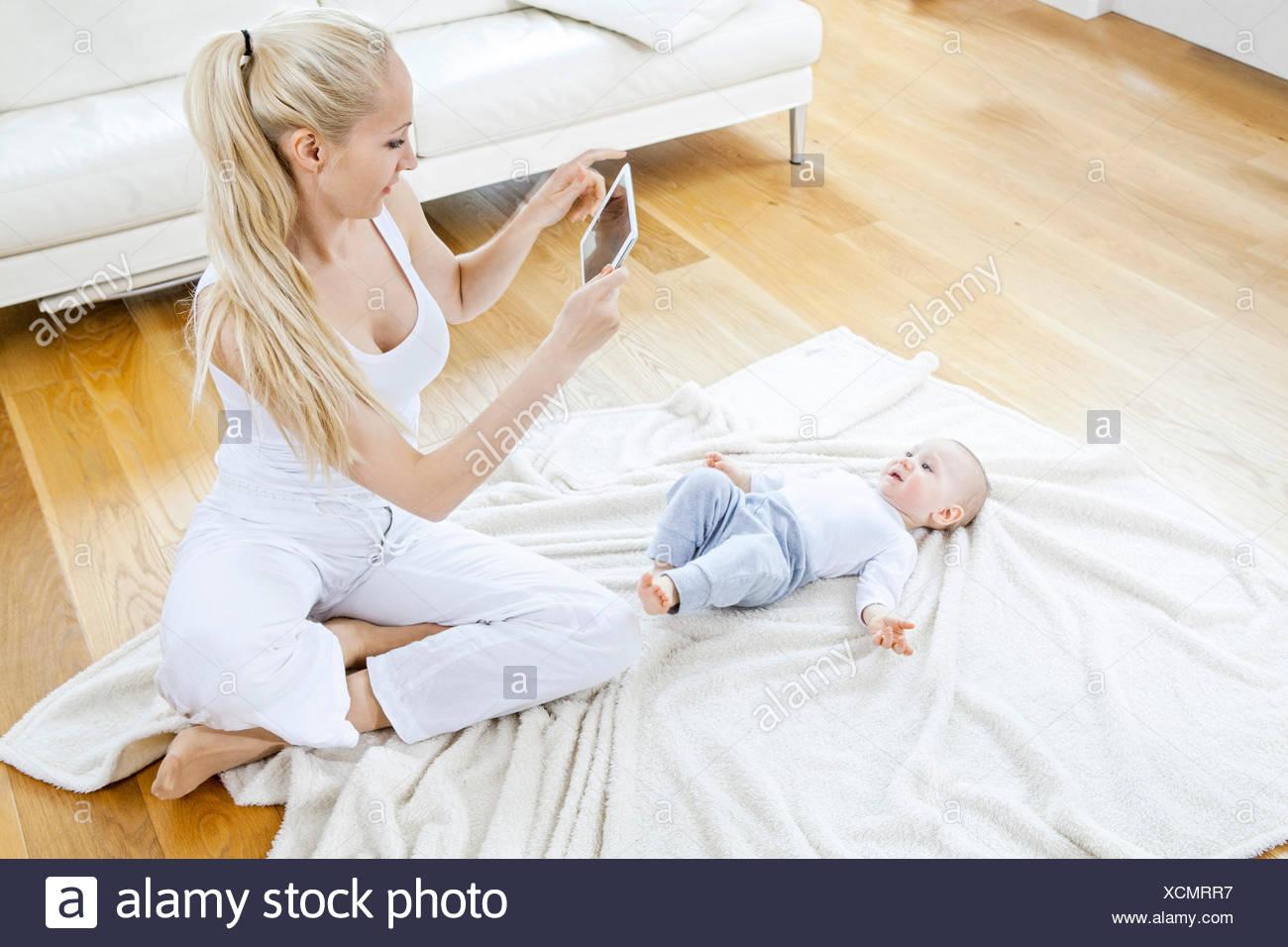 Madre di fotografare baby boy con tavoletta digitale Immagini Stock