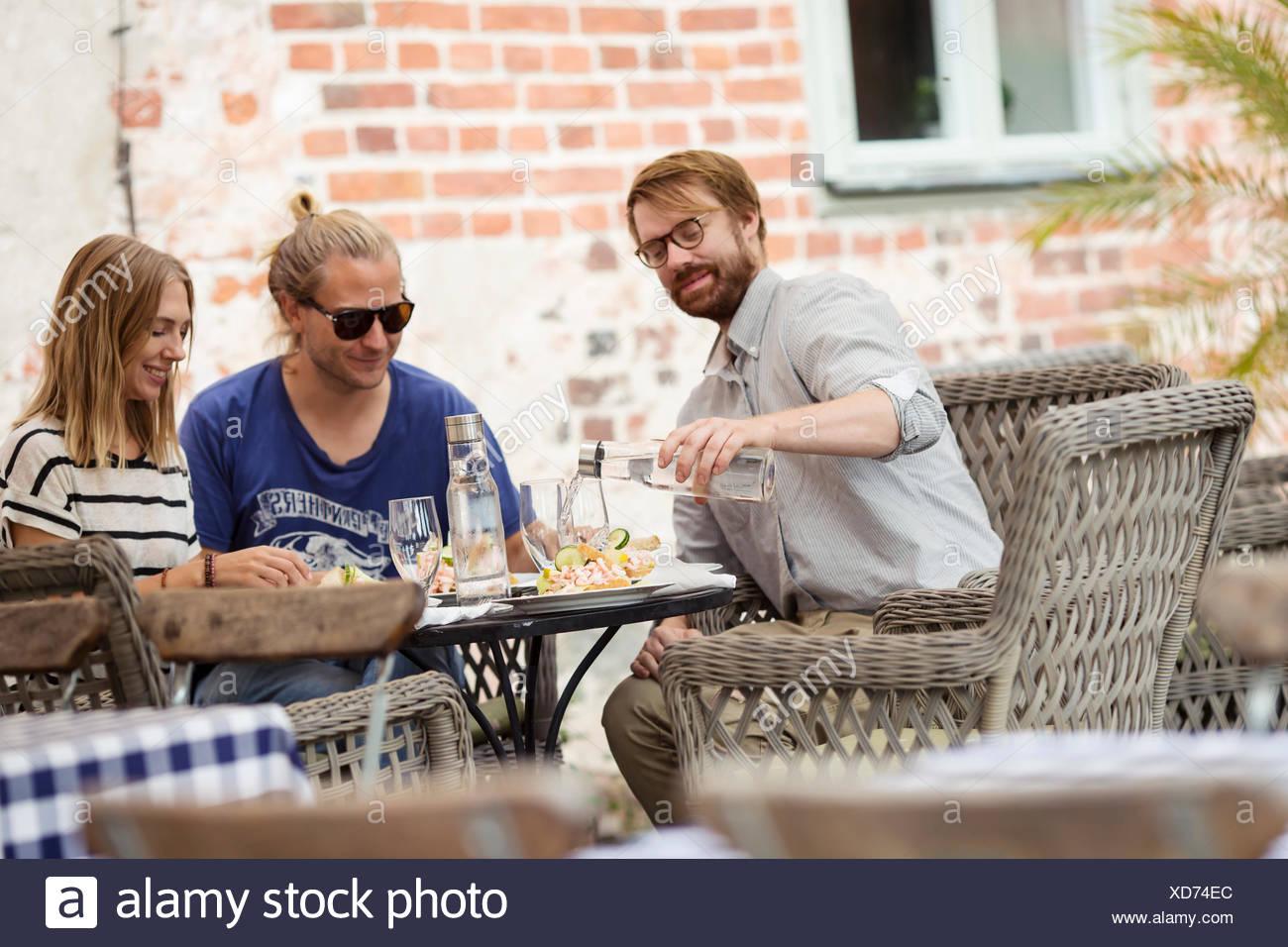 La Svezia, Skane, tre persone presso il cafe di mangiare il pranzo Immagini Stock