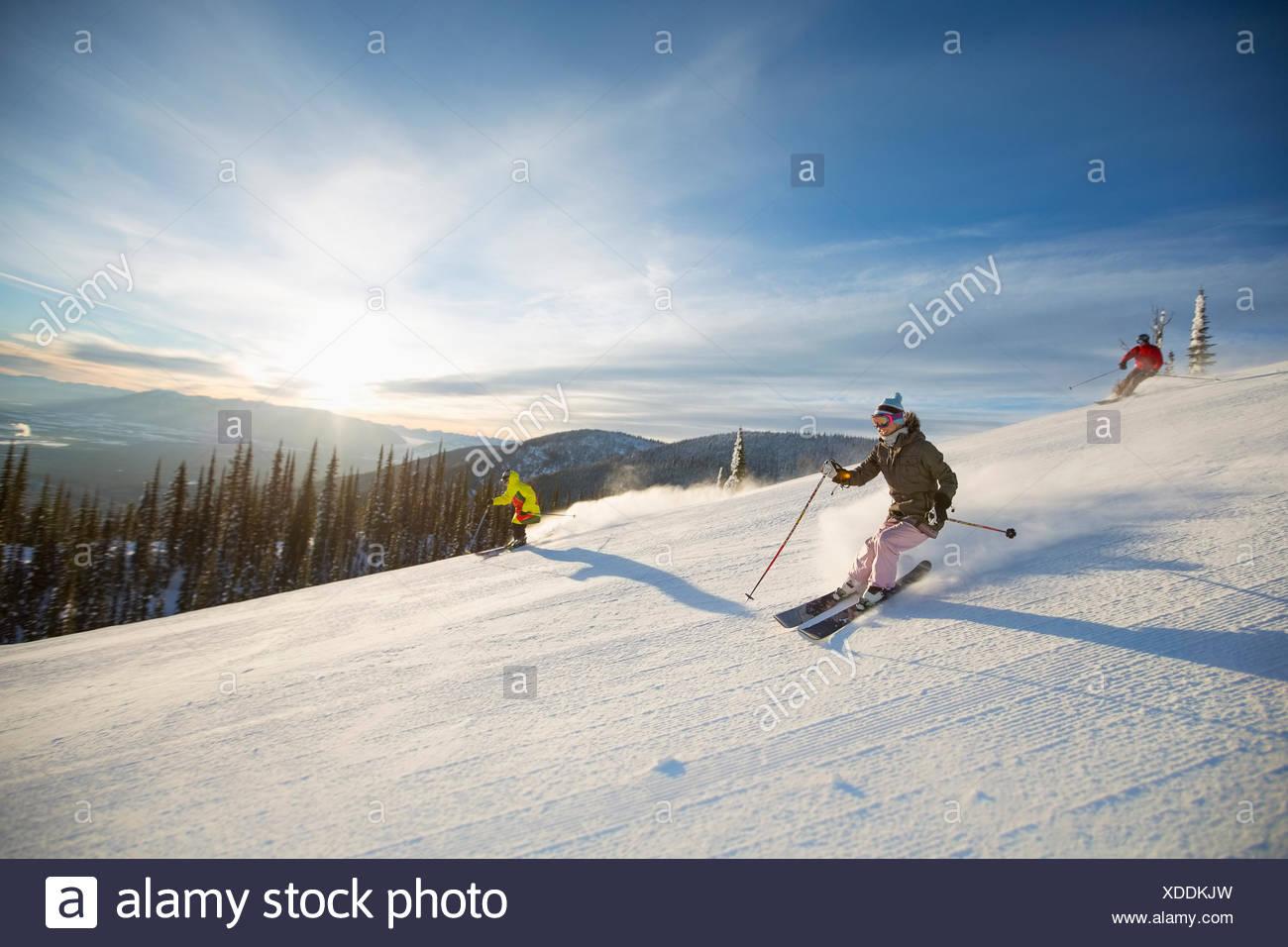 Tre persone sulla pista da sci al sole Immagini Stock