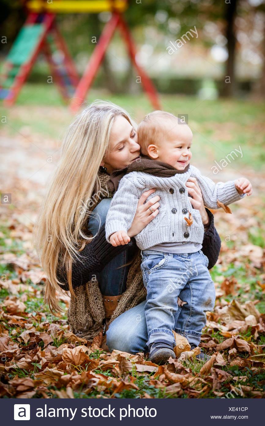 Madre e figlio giocare con foglie di autunno, osijek, Croazia Immagini Stock