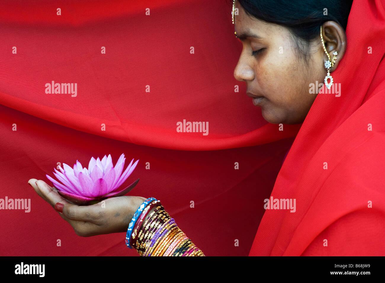 Mulher indiana oferecendo uma Nymphaea Tropical flor nenúfar em um vermelho sari Imagens de Stock