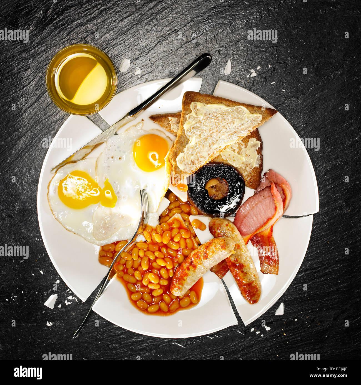 Um pequeno-almoço completo contendo bacon, ovos, salsichas, feijão cozido, cogumelos e torradas Imagens de Stock