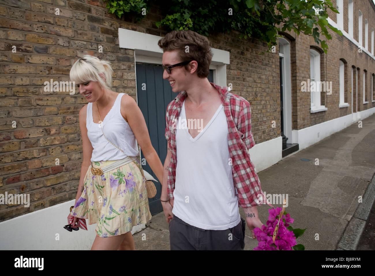 Casal a pé para casa do mercado de flores no Verão, Londres, Inglaterra, Reino Unido, Europa Imagens de Stock