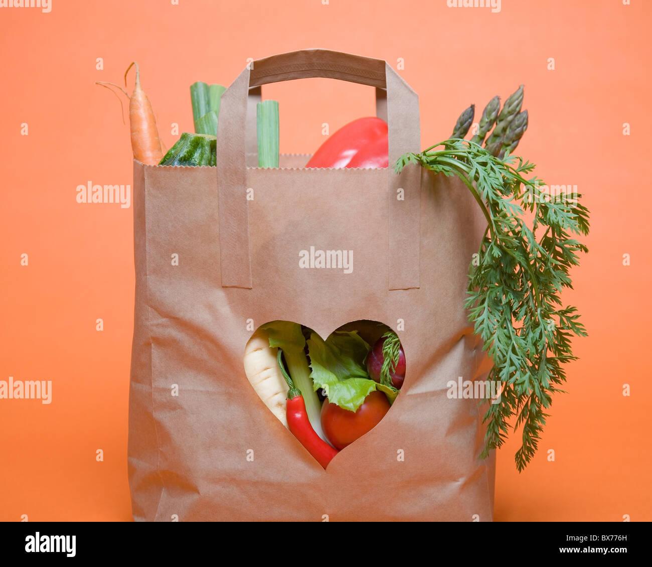 Produtos hortícolas no saco com símbolo de coração Imagens de Stock