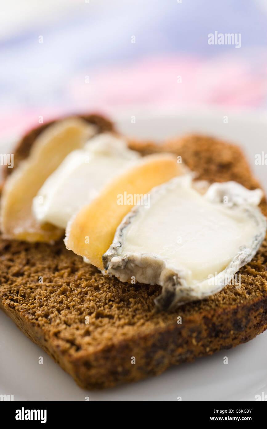 Fatias de pão de especiarias com queijo de cabra e balas de gengibre Imagens de Stock