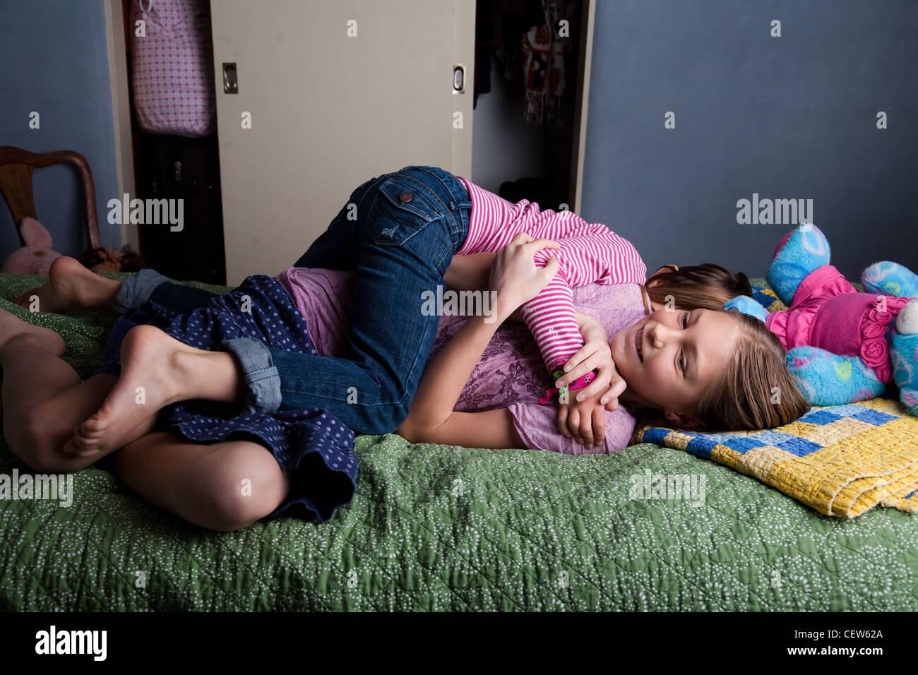 Duas meninas wrestling sobre a cama Imagens de Stock