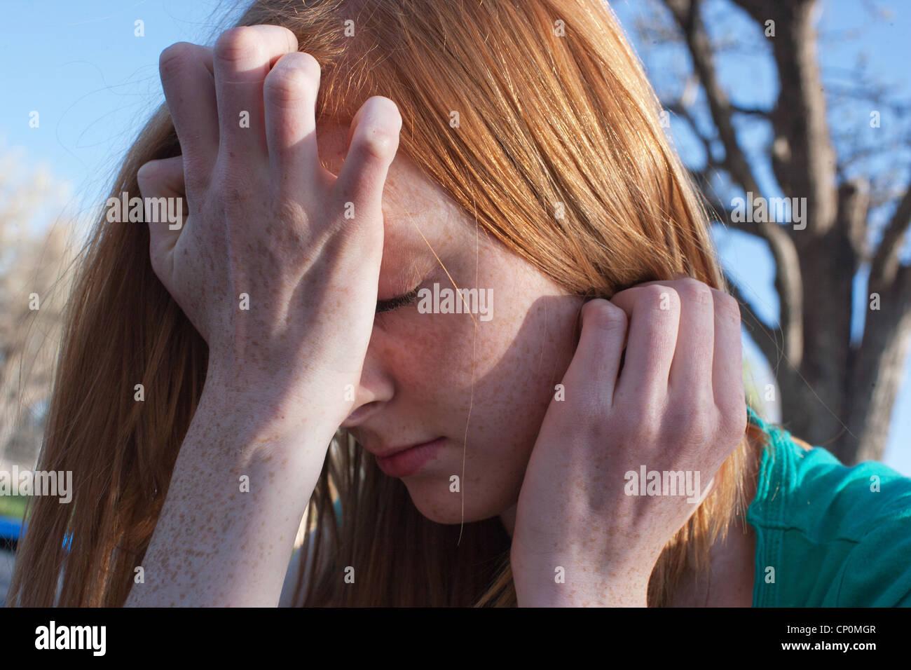Perto de uma menina de dezesseis anos vivenciando a ansiedade e cobrindo o seu rosto com as suas mãos ao ar Imagens de Stock
