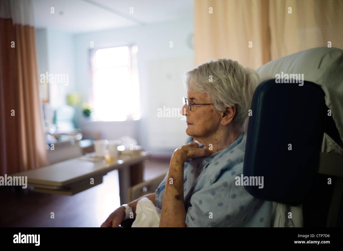 Antiga mulher sentada em cadeira de rodas no hospital. Imagens de Stock