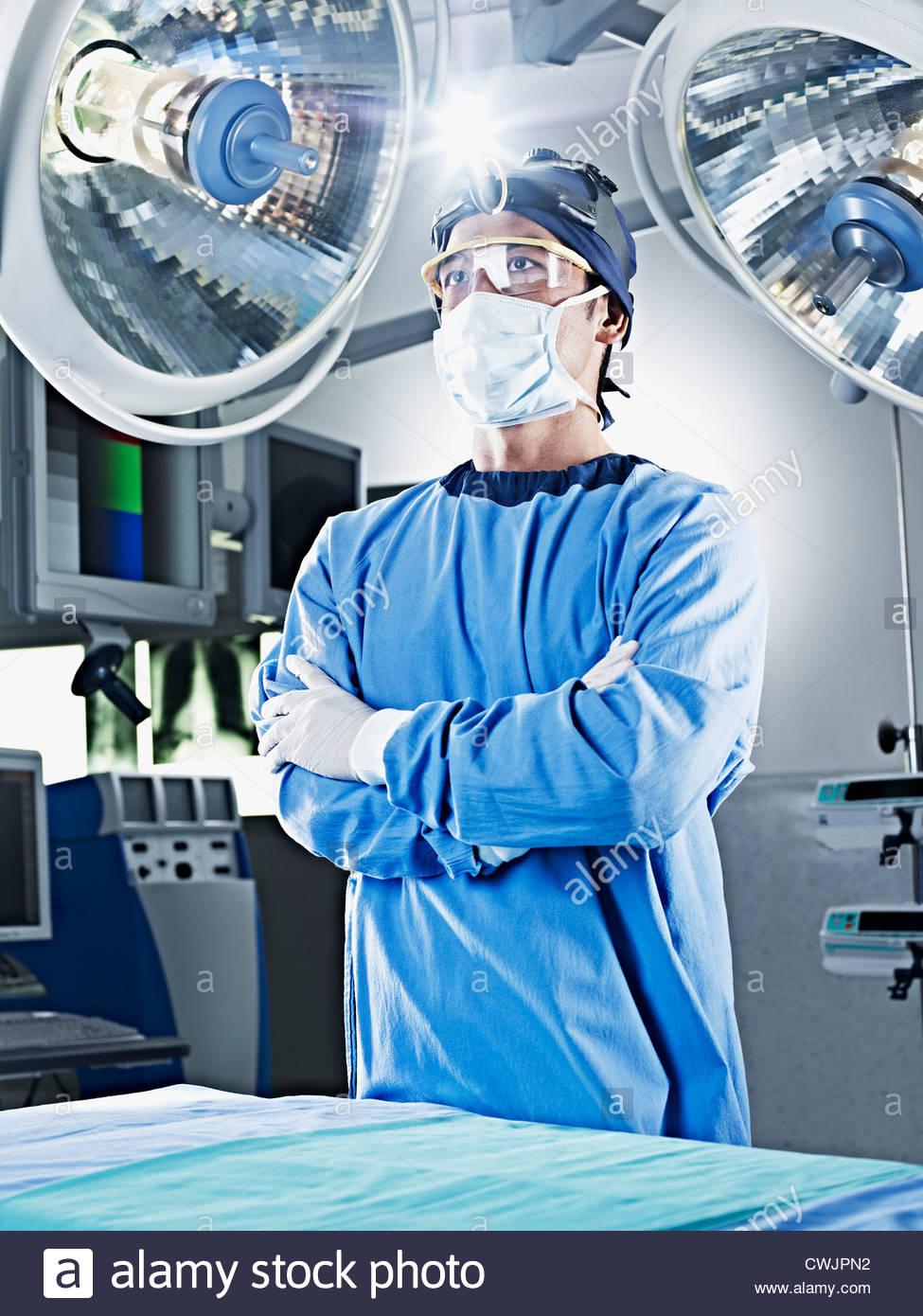 Retrato de graves cirurgião com braços cruzados sob as luzes cirúrgico Imagens de Stock