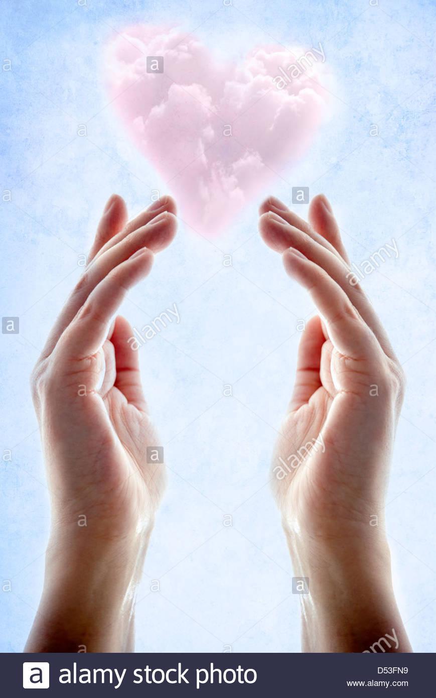 Mãos com rosa em forma de coração flutuante nuvem acima deles Imagens de Stock
