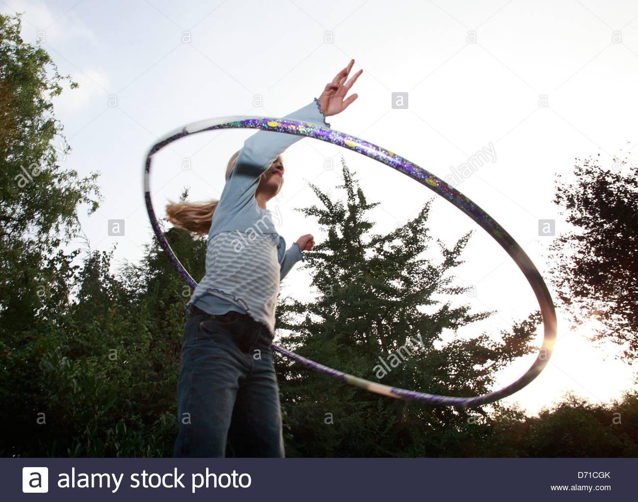 Ângulo Baixo vista de uma rapariga a brincar com um hula hoop Imagens de Stock
