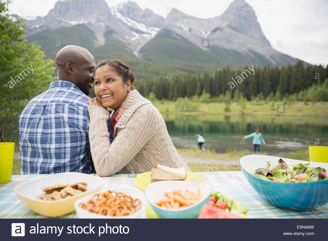 Casal sentado na mesa de piquenique perto do lago Imagens de Stock