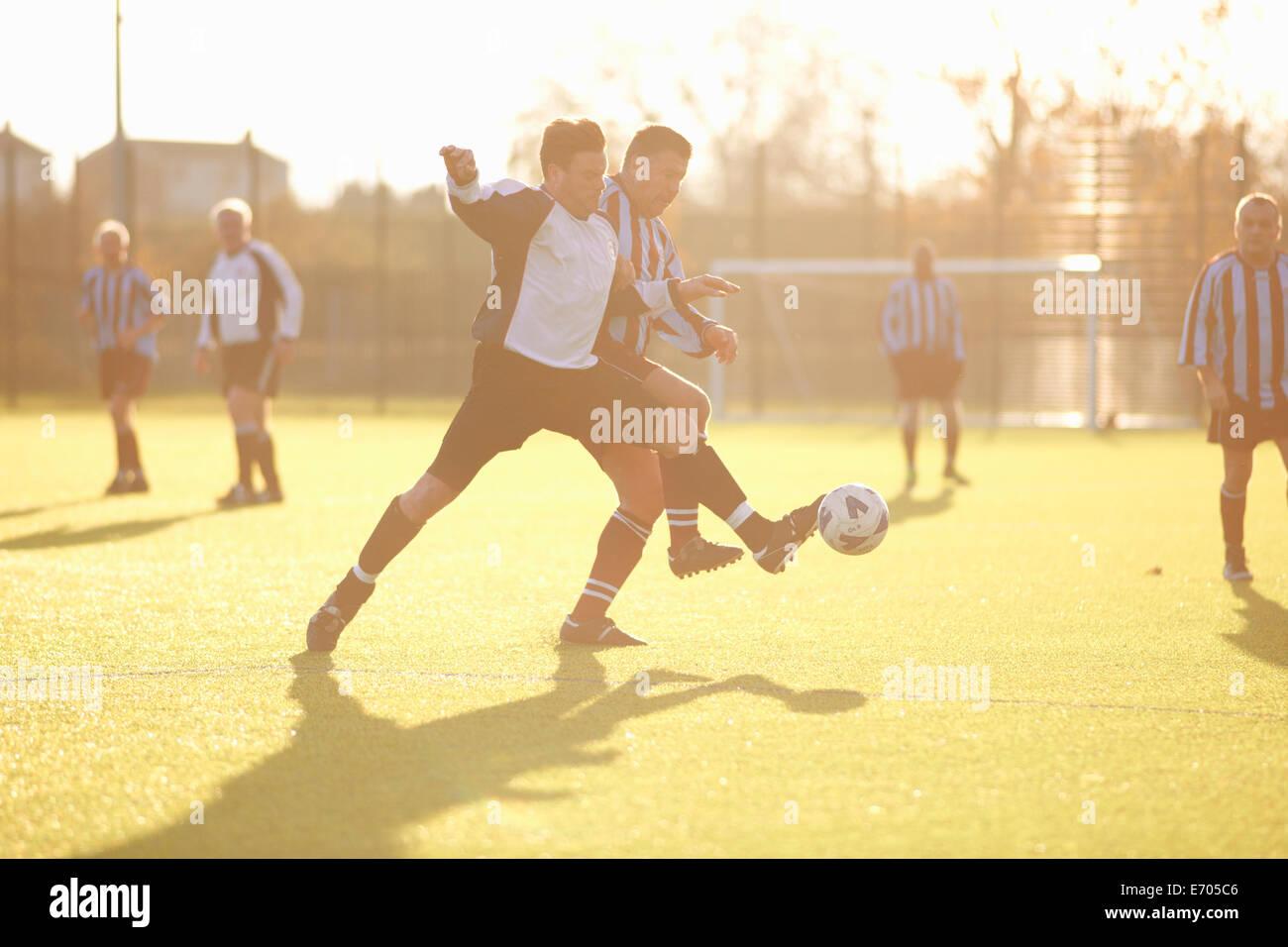 Jogadores de futebol lutam pela bola Imagens de Stock