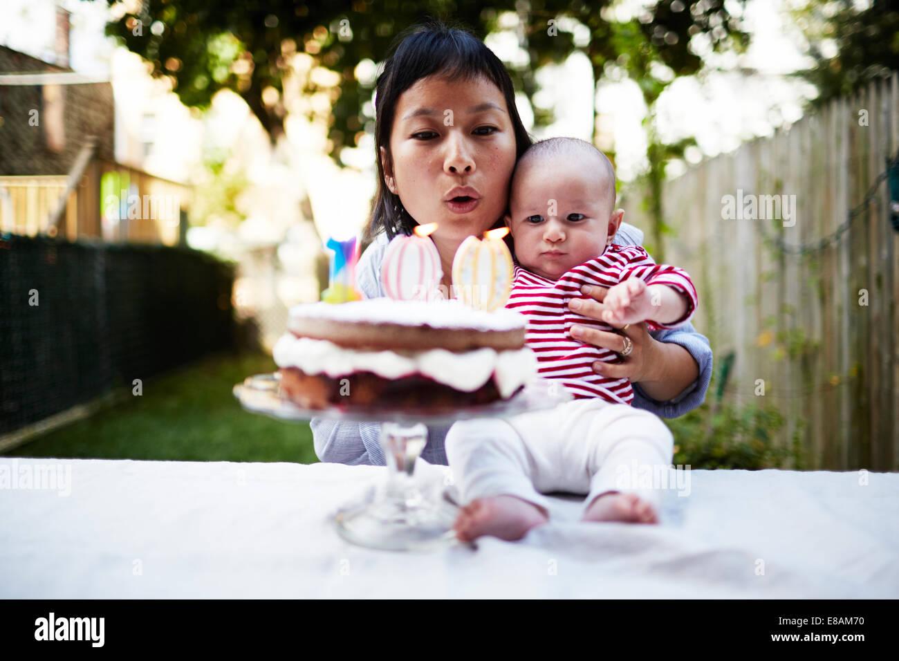 Mãe segurando o bebé filho, soprando velas no bolo Imagens de Stock