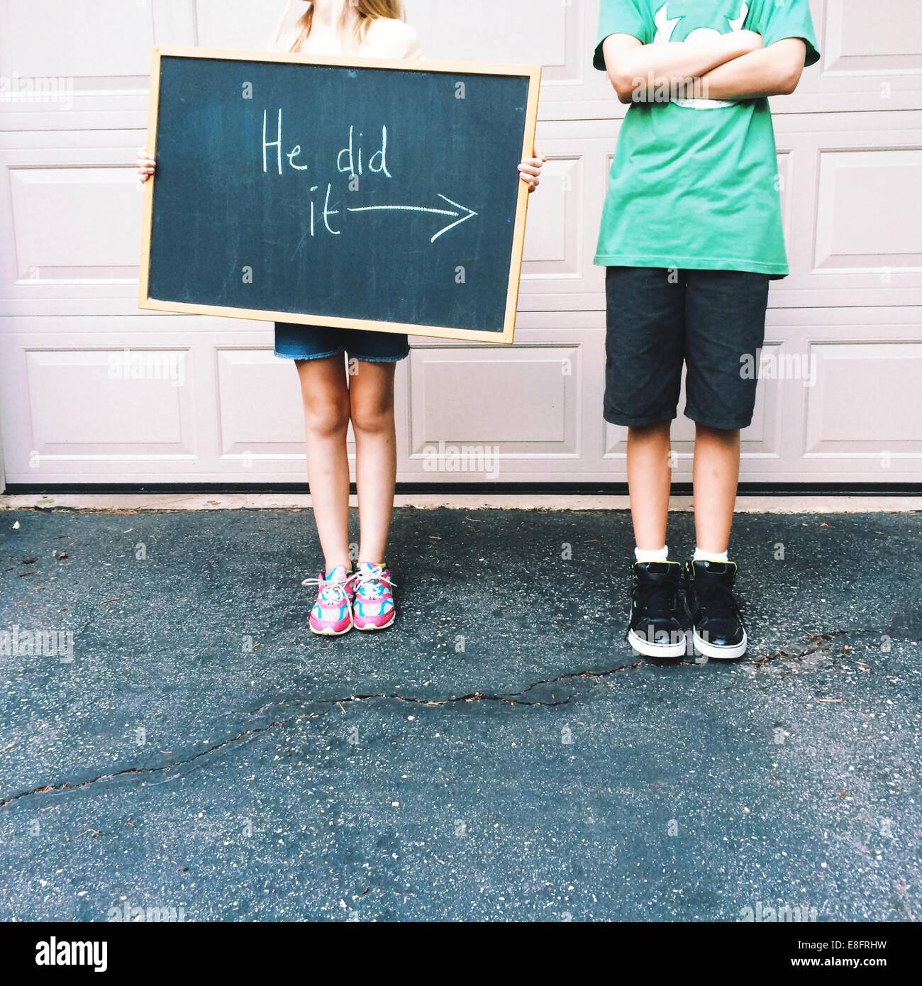 Menina (8-9) e boy (12-13) com a Blackboard assinar Imagens de Stock
