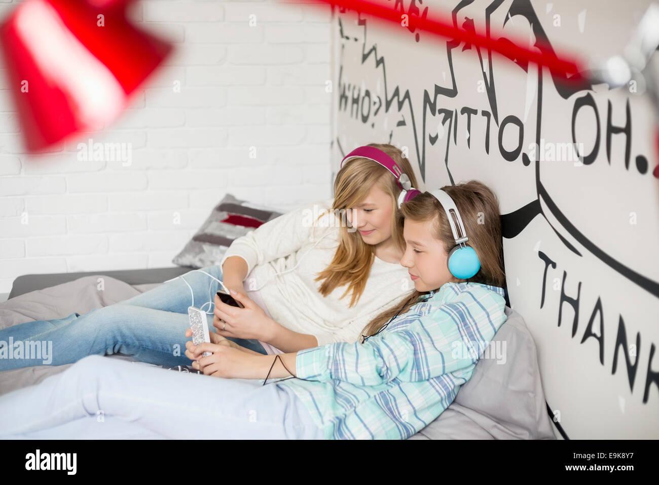 Relaxado irmãs para ouvir música em casa Imagens de Stock