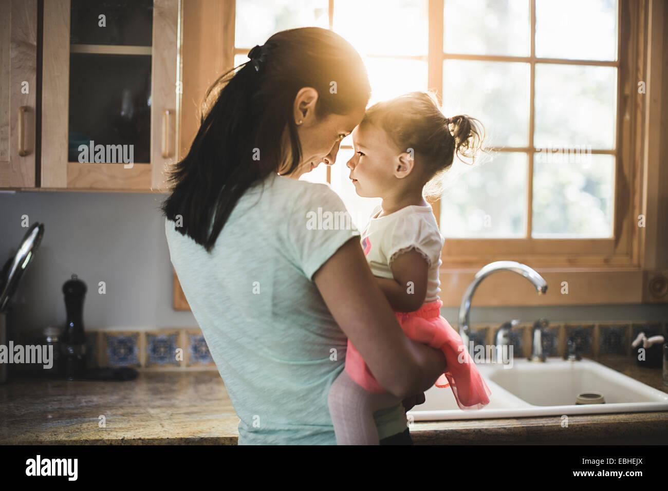 Mãe e filha jogando na cozinha Imagens de Stock