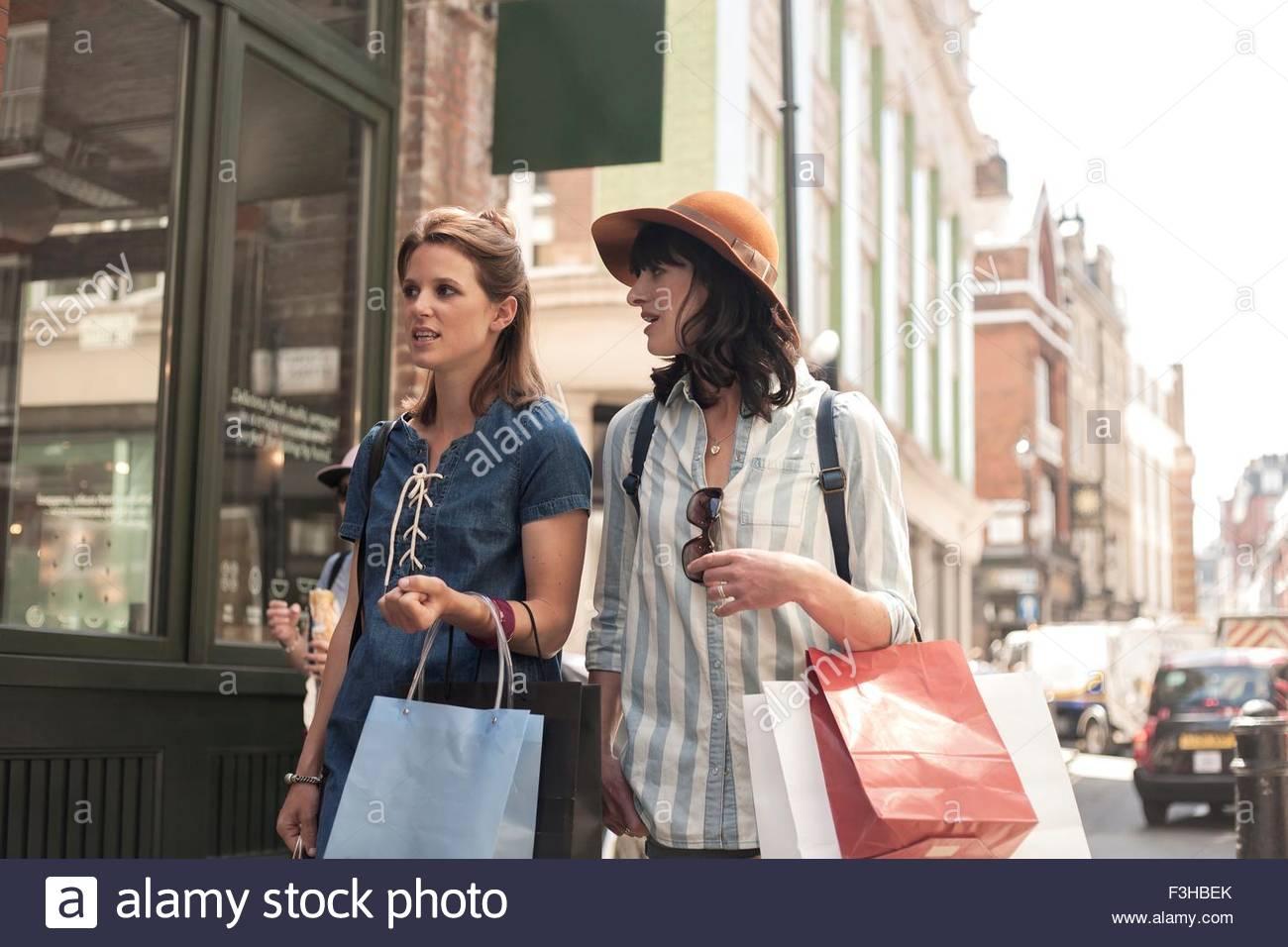 Duas mulheres transportando sacos de compras procurando na loja de vidros Imagens de Stock