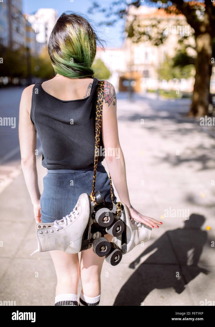 Espanha, Gijon, vista traseira da jovem mulher verde com cabelos tingidos transportando patins em linha sobre o Imagens de Stock