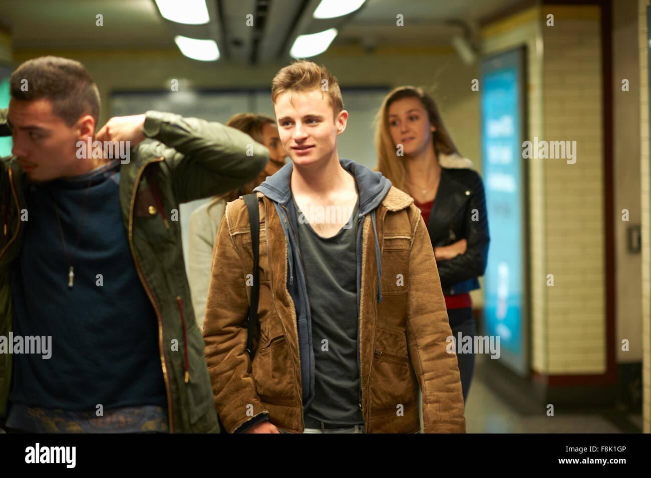 Quatro adultos jovens amigos a pé através da estação de metro de London, Londres, Reino Unido Imagens de Stock