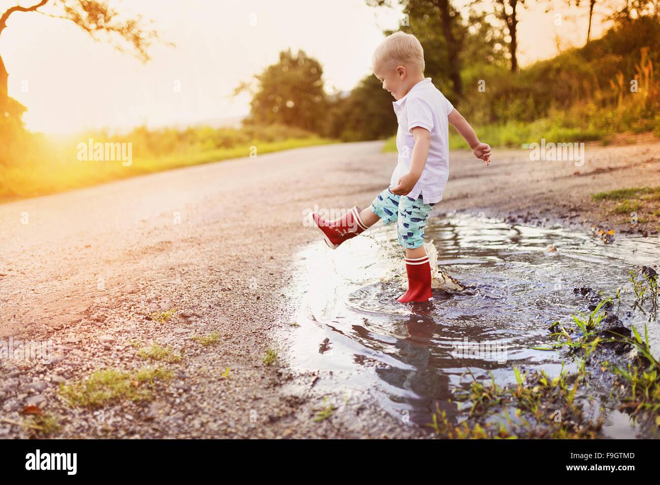 Little boy jogar fora em uma poça Foto de Stock