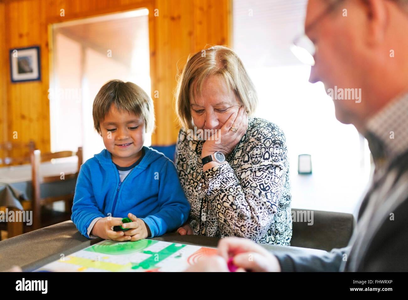 Avós jogando ludo seu neto Imagens de Stock